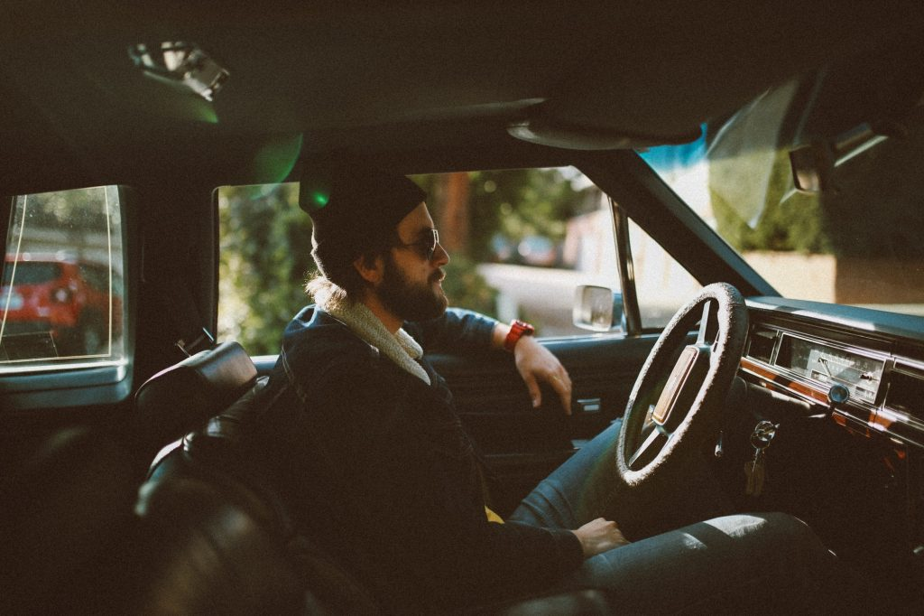 Fashionable young hipster boy sitting in old vintage car