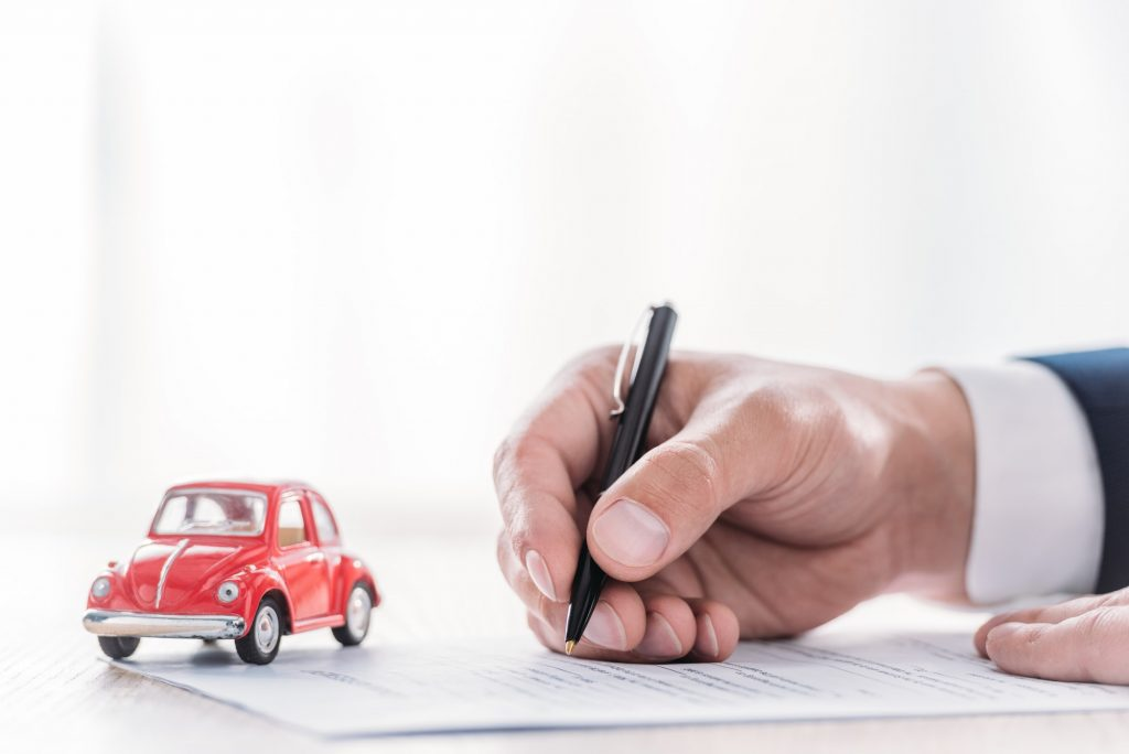 partial view of car dealer writing in loan agreement near red miniature car on tabletop